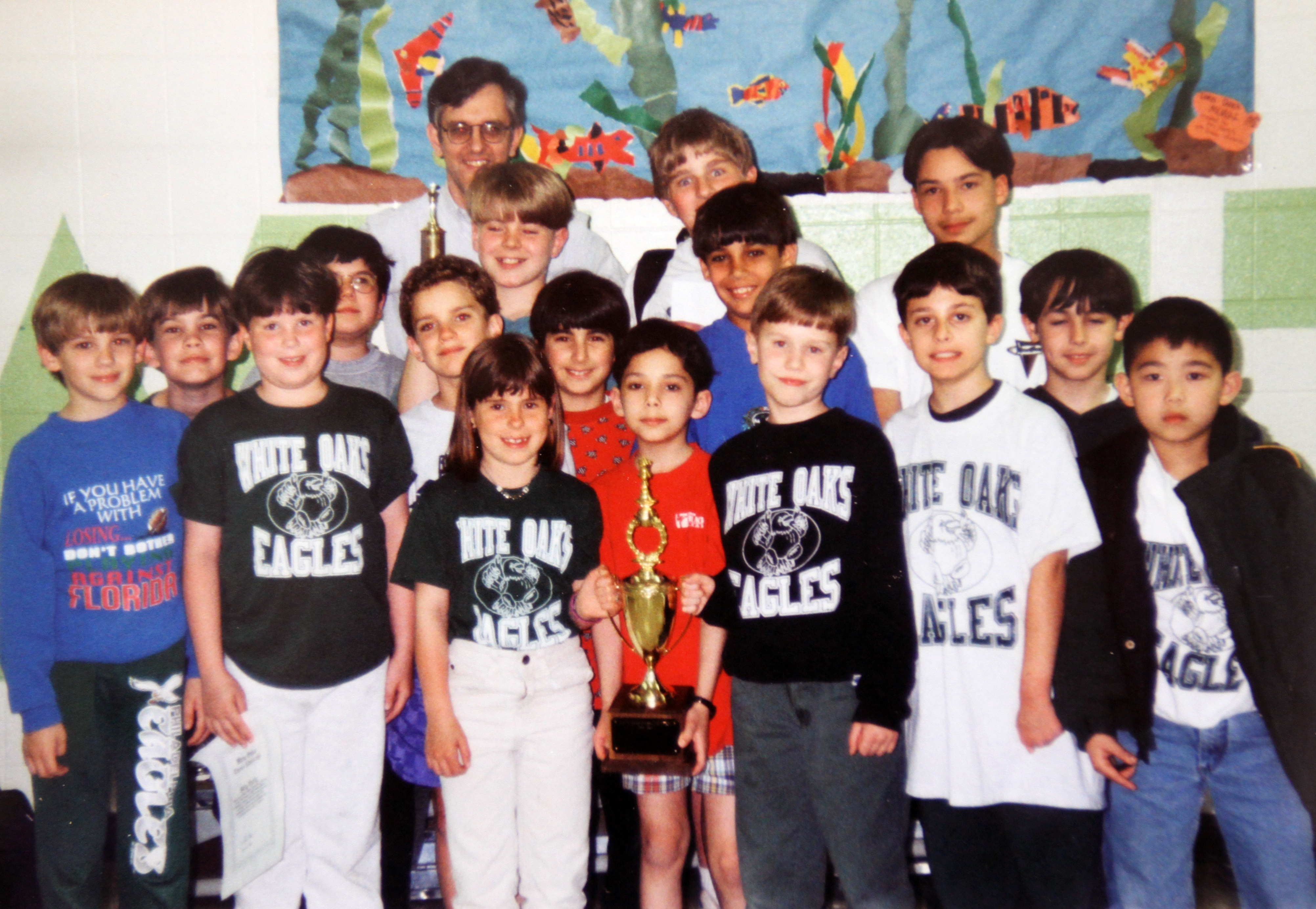 Photograph of the championship-winning chess team posing with their trophy.