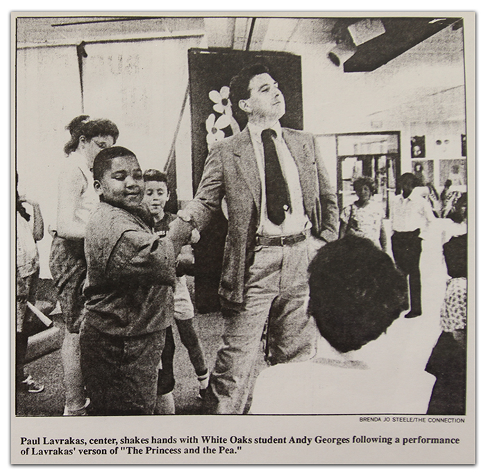 Black and white photograph from a newspaper article showing Paul Lavarakas shaking hands with White Oaks students.