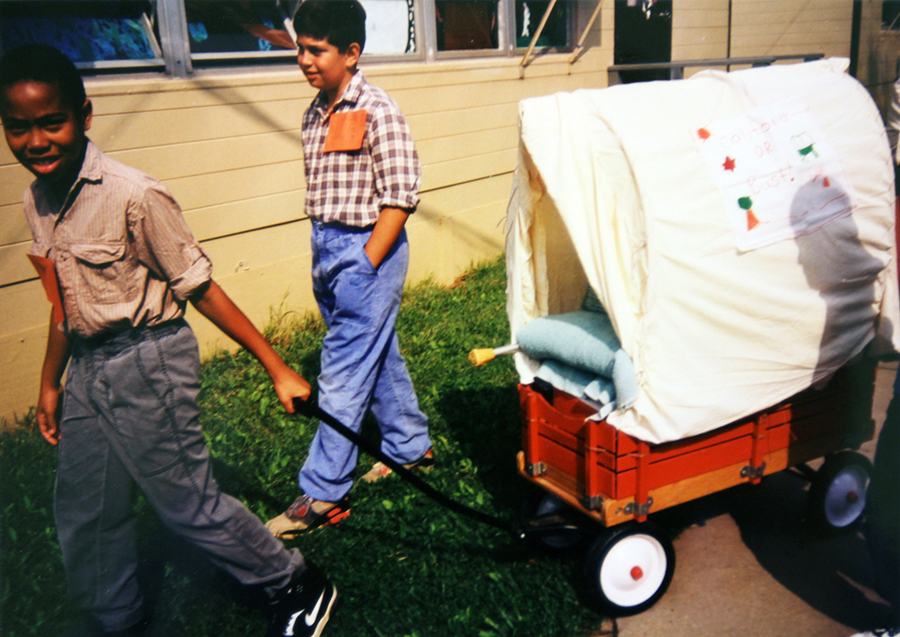 Photographs of two students pulling a Red Flyer wagon decorated to look like a Conestoga wagon.